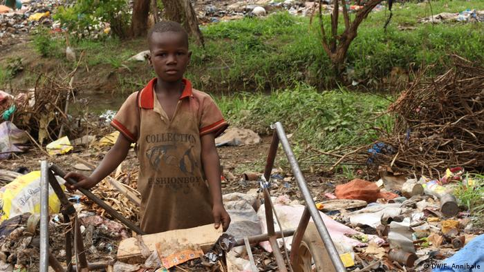 A young boy among the garbage by a stream