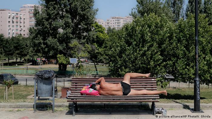 Homem deitado de sunga em banco de Bucareste