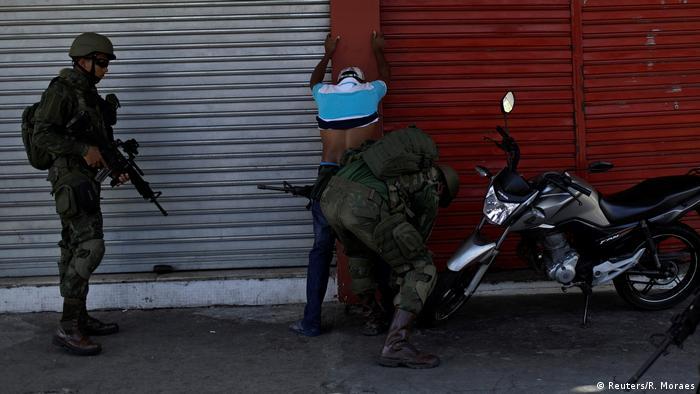 Ein Mann steht mit erhobenen Armen an einer Wand und wird von einer Einsatzkraft durchsucht (Foto: Reuters)