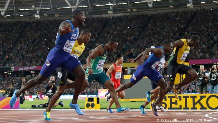 Gatlin (e) festeja sua vitória, seguido de Coleman (também de azul) e Bolt