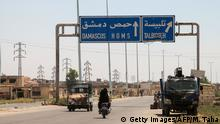 A picture taken on August 3, 2017 shows vehicles driving past a roadsign that says Talbiseh in the eponymous central Syrian rebel-held town, north of Homs, along the highway between the capital Damascus and the central city of Homs. A ceasefire between government forces and rebels went into effect in part of central Syria on August 3, 2017 after Russia struck a deal with the opposition on a safe zone in the northern parts of Homs province. The truce is the third to be established in Syria, which has been ravaged by six years of civil war that have left more than 300,000 people dead. / AFP PHOTO / MAHMOUD TAHA (Photo credit should read MAHMOUD TAHA/AFP/Getty Images)