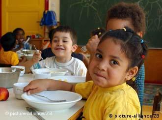 A diverse group of children eat lunch in a Berlin kindergarten classroom