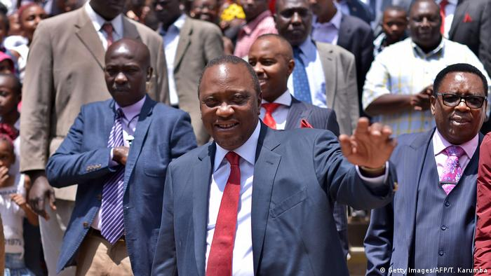 A smiling Uhuru Kenyatta with a crowd of supporters