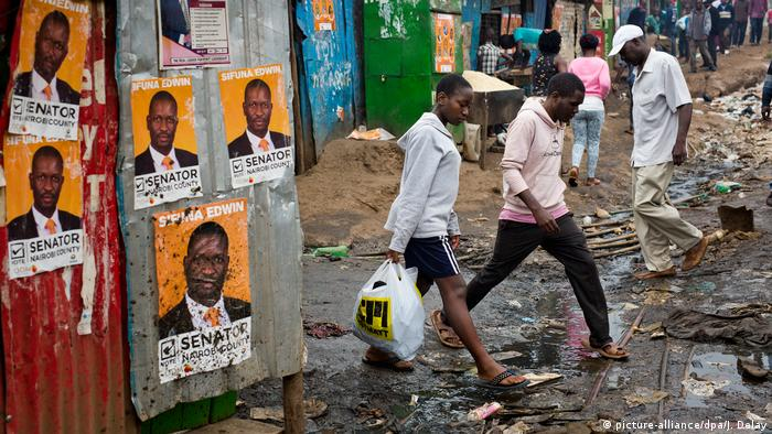 people walking past campaign posters (picture-alliance/dpa/J. Delay)