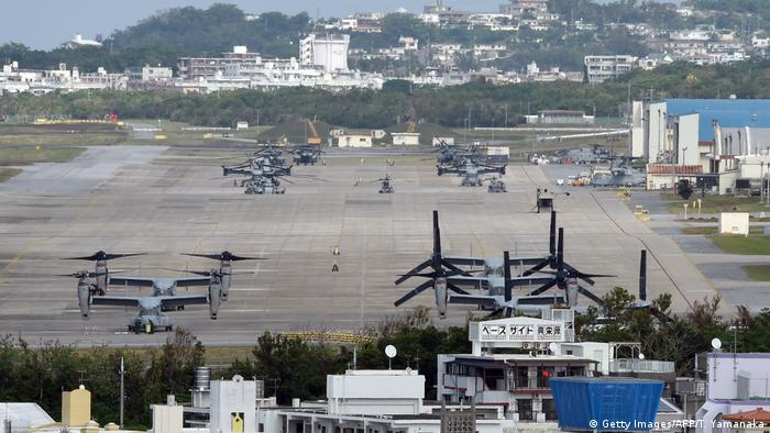 A wide shot of the US military base in Okinawa shows Osprey aircraft parked in formation.