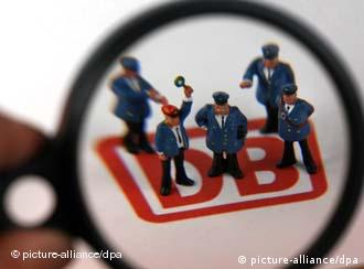 Plastic figures of Deutsche Bahn employees seen under a magnifying glass