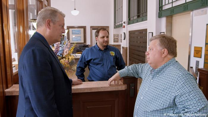 Al Gore listening to two men - scene from An Inconvenient Sequel a film by Bonni Cohen and Jon Shenk