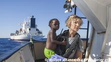 A Proactiva Open Arms nurse carries a child after the NGO rescued a migrant boat off the Libyan coast in August 2017. (picture alliance/dpa/AP/A. Surinyach)