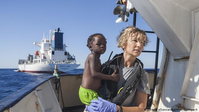 A Proactiva Open Arms nurse carries a child after the NGO rescued a migrant boat off the Libyan coast in August 2017.