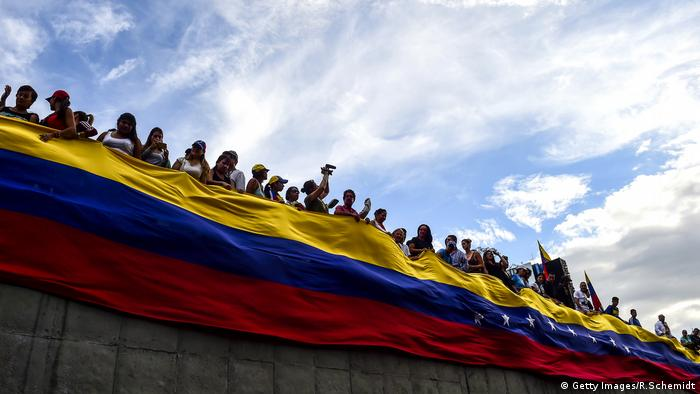 Opposition activists hold the Venezuelan flag