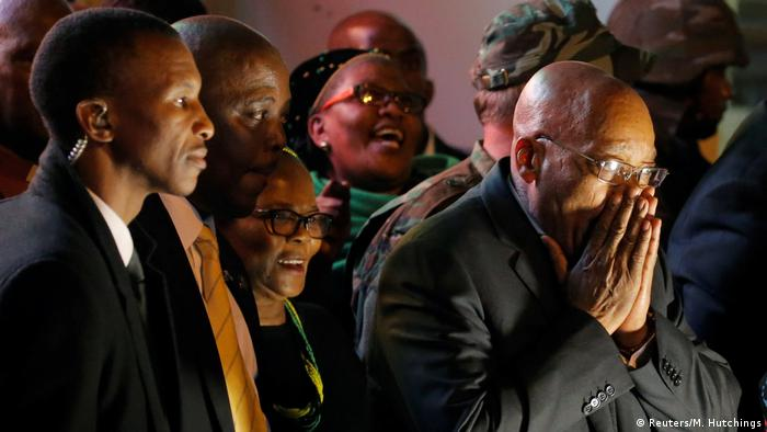 Jacob Zuma claps his hands over his mouth as people behind him look on (Reuters/M. Hutchings)