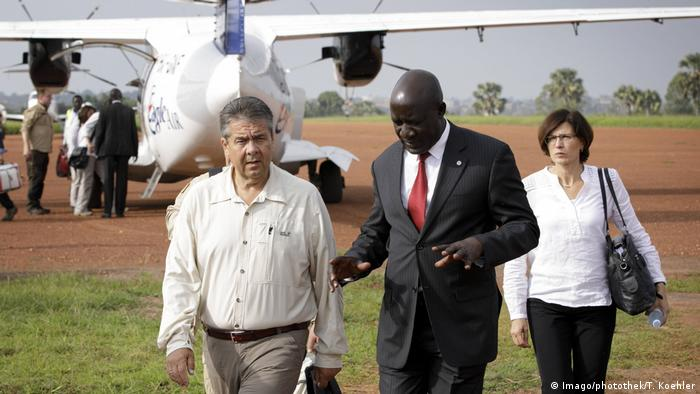 Germanys Foreign Minister Sigmar Gabriel talks to the Ugandan minister for refugees Francis Ecweru ImagophotothekT Koehler