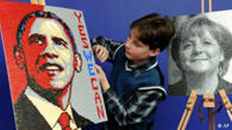 At the International toy fairs in Nuremberg, Germany, a child looks at an Obama mini plug photo. (AP Photo/Christof Stache)