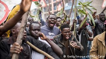 Protesters shouting and shaking sticks in Mathare slum