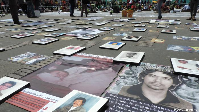 Photos of people killed in cases of 'false positives' are laid out in rows on Bogota's main square