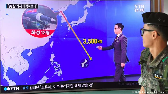A South Korean soldier walks past a television screen showing a graphic of the distance between North Korea and Guam
