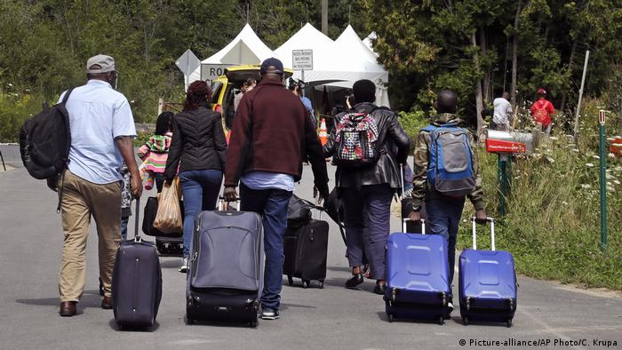 A family from Haiti approach a tent in Saint-Bernard-de-Lacolle