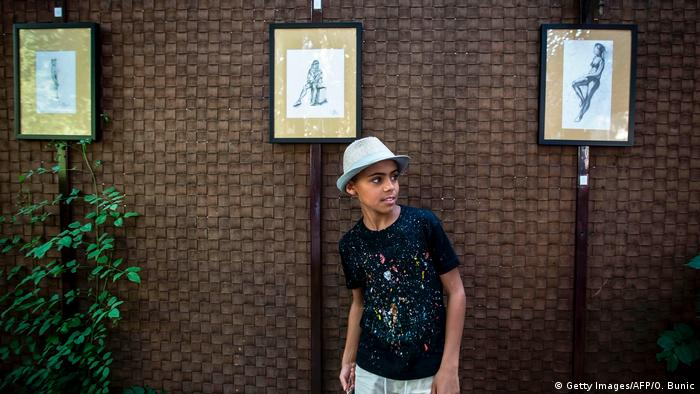 Farhad Nouri poses in front of his drawings during his first exhibition in Belgrade