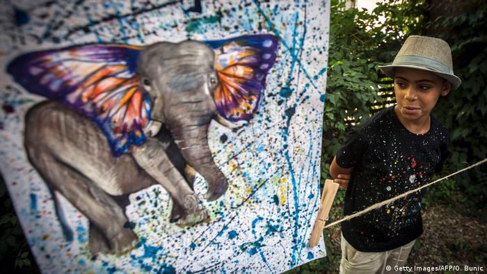 Farhad Nouri from Afghanistan looks at one of his art works in Belgrade