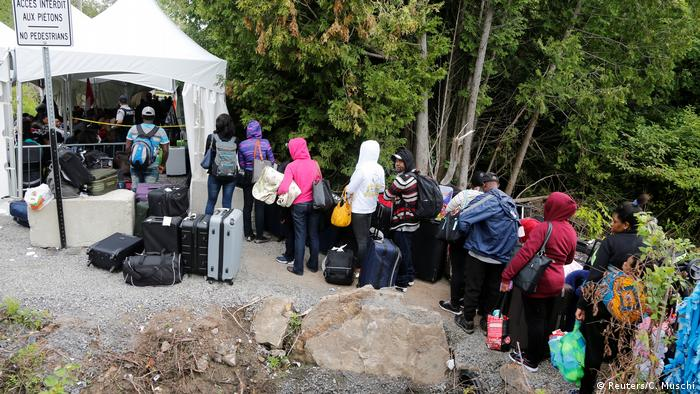 Asylum seekers walk across the US-Canadian border at Roxham Road