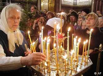 Russian Tamara Smirnova places a candle during a Christmas service in the Christ the Savior Cathedral in Moscow