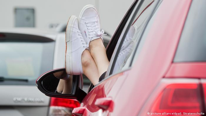 Person with their feet propped up outside a car window (picture-alliance/dpa/J. Stratenschulte)