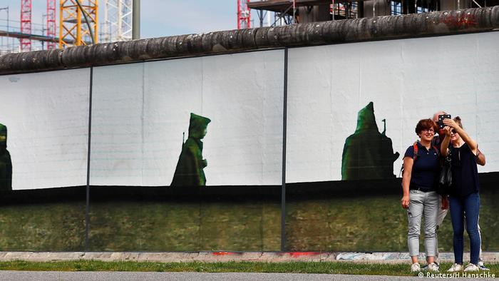 People taking selfies in front of art installation along Berlin Wall