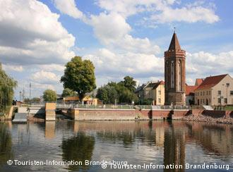 The picture looks out over a bridge and a few buildings in Brandenburg