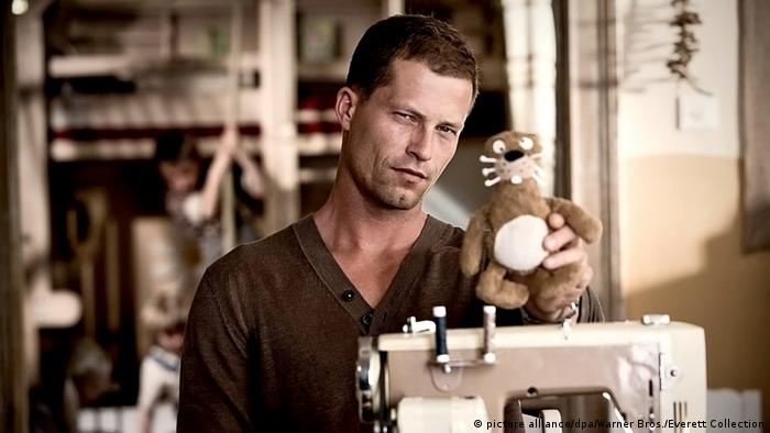 Film still of Rabbit without Ears with Til Schweiger holding a toy rabbit without ears (picture alliance/dpa/Warner Bros./Everett Collection)