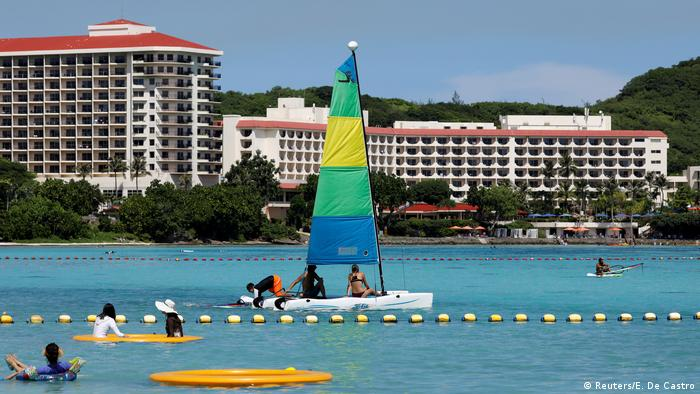 Hotels in the background as people swim and sail in the foreground - Tourismus (Reuters/E. De Castro)