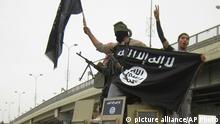 FILE - in this Sunday, March 30, 2014, file photo, Islamic State group militants hold up their flag as they patrol in a commandeered Iraqi military vehicle in Fallujah, 40 miles (65 kilometers) west of Baghdad, Iraq. The fall of Fallujah in January 2014 started the Islamic State group's dramatic blitz across Iraq. In June, the extremists captured Iraq's second-largest city, Mosul, then swept south toward Baghdad in a march that put almost all the Sunni-majority regions of northern and western Iraq into its hands. The Iraqi military crumbled, with troops often dropping their weapons and fleeing. (AP Photo, File) |