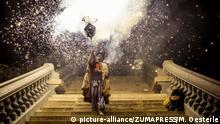 Symbolbild: Situation aus dem Fest Diables de Sitges aus Sitges in Spanien: Ein als Teufel verkleideter Mann hält eine Art Standarte in der Hand und geht die Stufen einer Kirche hinab. Im Hintergrund ein großes Feuerwerk
