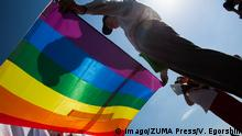 Activists hold up a rainbow flag against the sun at an LGBT Pride march in Saint Petersburg (Imago/ZUMA Press/V. Egorshin)