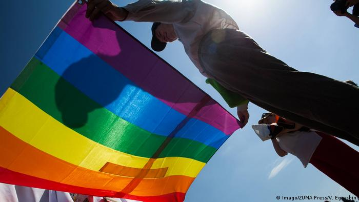 Activists hold up a rainbow flag against the sun at an LGBT Pride march in Saint Petersburg