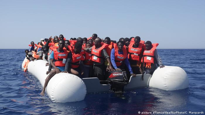Refugees and migrants are seen floating in an overcrowded rubber boat as they wait to be assisted by search and rescue crew members from NGO Sea-Eye on May 19, 2017 in international waters off the coast of Libya. (picture alliance/dpa/NurPhoto/C. Marquardt)