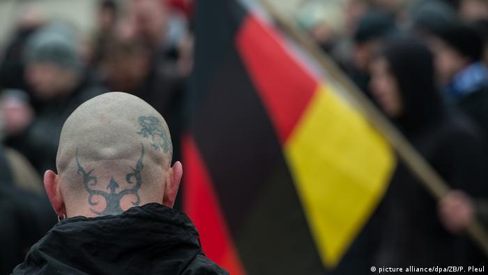 Ein rechter Lederkopf mit deutscher Flagge im Hintergrund während der Parade 2015