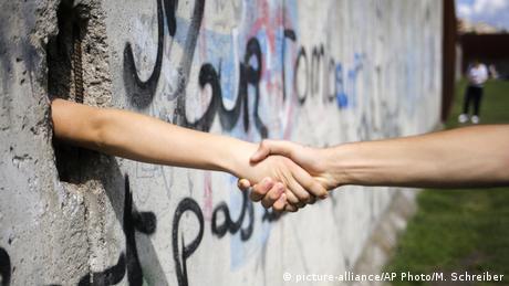 Durch ein Loch im Rest der Berliner Mauer schütteln zwei Personen ihre Hände