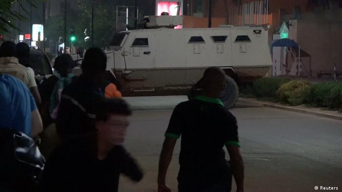 Civilians look at an armored vehicle blocking the street (Reuters )
