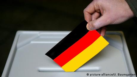A hand places the German flag in the ballot box (picture-alliance/U. Baumgarten)