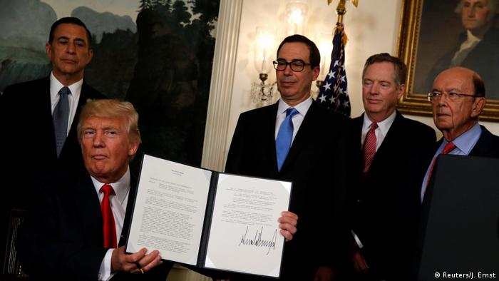 Trump holds the signed memo to start the review of trade issues with China