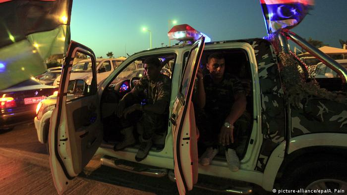 Soldiers from the al-Saiqa brigade sit inside a vehicle. The war crimes suspect sought by the ICC is a commander of the elite unit