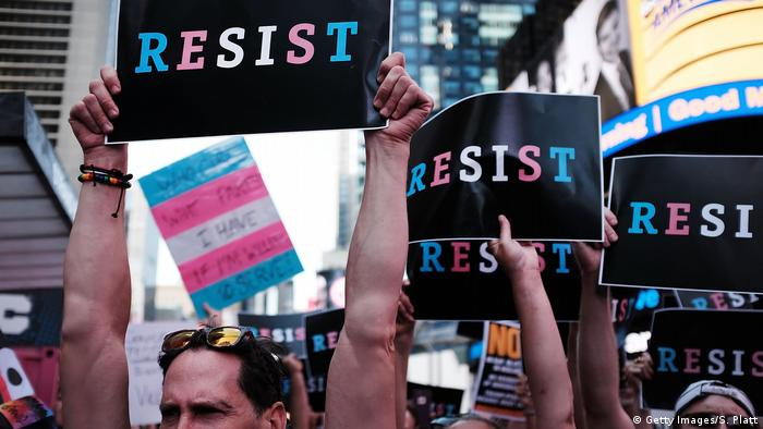 Protesters rally for transgender rights in New York City's Times Square carry signs that say, resist. (Photo by Spencer Platt/Getty Images)