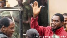 Zambian opposition leader Hakainde Hichilema waves to supporters from a police van as he leaves a courtroom in Lusaka on April 18, 2017. Hichilema's arrest on treason charges -- after his convoy allegedly refused to give way to the president's motorcade on a main road in the west of the country -- has fanned political tensions in Zambia. / AFP PHOTO / DAWOOD SALIM