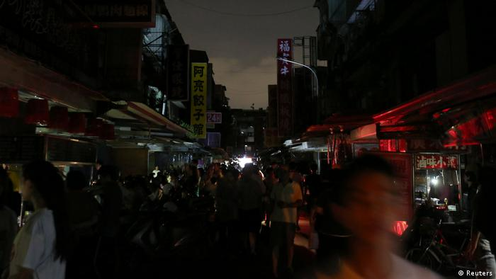 People walk on a street during a massive power outage in Taipei, Taiwan