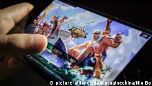 A Chinese mobile game player plays Tencent's mobile MOBA King of Glory or Honor of Kings on his smartphone in Beijing, China, 11 July 2017. All-night gaming marathons will soon end for some Chinese kids after internet giant Tencent began limiting daily playing times on its smartphone smash hit King of Glory to ensure children's healthy development. Young players will be restricted to one or two hours on the mobile online multiplayer battle game, which boasts 80 million daily users, as concerns grow in China that long periods online are posing a serious threat to the health of the country's youth. Users under 12 years old are now limited to one hour of play a day, and will not be permitted to sign in after 9 pm, Tencent said in a statement over the weekend. The move went into effect on Tuesday. Users between 12 and 18 years old are limited to two hours per day. Foto: Niu Bo/Imaginechina/dpa |