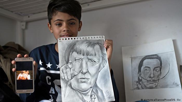 Menino segurando retrato a lápis de Angela Merkel