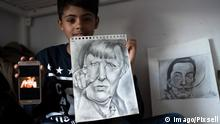 10-year-old migrant from Afghanistan Farhad Nouri holds up a drawing of German Chancellor Angela Merkel