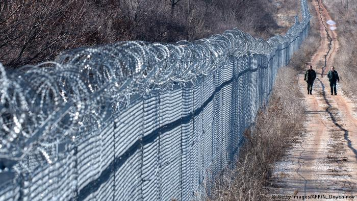 Bulgarian border police patrol next to a barned wire fence erected on the Bulgarian-Turkish border near the town of Lesovo