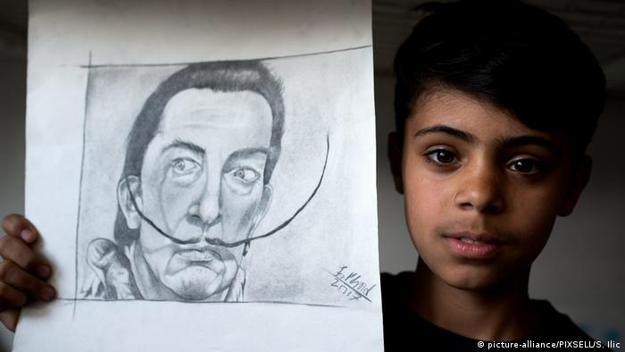 Farhad Nouri holds his drawing of Salvador Dali