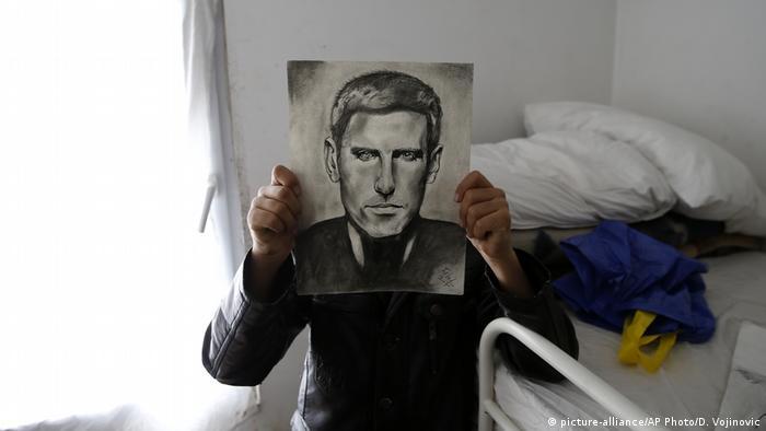 Farhad Nouri poses with a drawing portrait of Serbian tennis player Novak Djokovic
